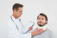 Male doctor examining a patients sprained neck Stock Photography