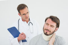Male doctor examining a patients sprained neck Stock Image