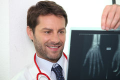 Male doctor examining x-ray image. Male doctor stood smiling whilst examining x-ray image Royalty Free Stock Image