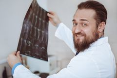 Male doctor examining x-ray scan at his office stock photos