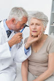 Male doctor examining senior patient's ear Royalty Free Stock Images