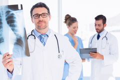 Male doctor examining xray with colleagues behind Royalty Free Stock Photo