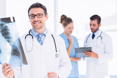 Male doctor examining xray with colleagues behind Royalty Free Stock Image