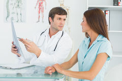 Male doctor explaining lungs xray to female patient. In the medical office royalty free stock photography