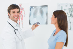 Male doctor explaining lungs xray to female patient. Portrait of a smiling male doctor explaining lungs xray to female patient in the medical office stock image