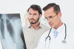 Male doctor explaining lungs xray to patient. In the medical office stock photos