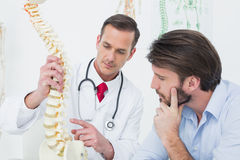 Male doctor explaining the spine to a patient Royalty Free Stock Photo
