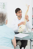 Male doctor explaining the spine to a patient Royalty Free Stock Photos