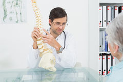 Male doctor explaining the spine to a patient Royalty Free Stock Image