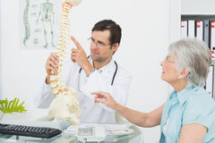 Male doctor explaining the spine to a senior patient Stock Photo
