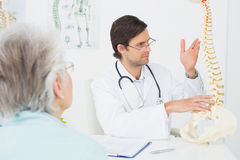 Male doctor explaining the spine to a senior patient Stock Image