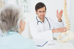 Male doctor explaining the spine to a senior patient Stock Photos