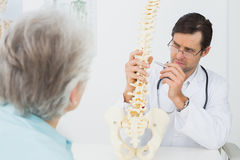 Male doctor explaining the spine to a senior patient Royalty Free Stock Photography