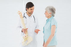Male doctor explaining the spine to a senior patient Royalty Free Stock Images