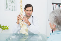Male doctor explaining the spine to a senior patient Royalty Free Stock Image