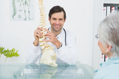 Male doctor explaining the spine to a senior patient Royalty Free Stock Photos