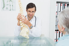 Male doctor explaining the spine to a senior patient Stock Photography