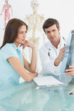 Male doctor explaining spine xray to female patient Royalty Free Stock Images