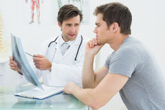 Male doctor explaining spine xray to patient Stock Image