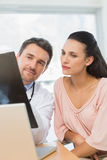 Male doctor explaining xray report to a patient Stock Photography