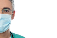 Male doctor with face mask. Cropped image of physician with surgical mask Royalty Free Stock Photography