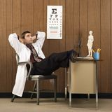 Male doctor with feet on desk. Royalty Free Stock Images