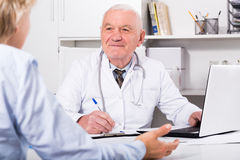 Male doctor with female client. Old female visitor consulting smiling aged men doctor in hospital Royalty Free Stock Photos