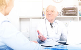Male doctor with female client. Old female visitor consulting smiling aged men doctor in hospital Royalty Free Stock Images