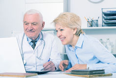 Male doctor with female client. Old female visitor consulting smiling aged men doctor in hospital Royalty Free Stock Photography