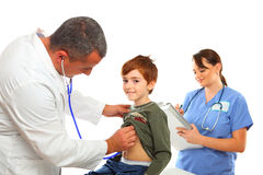 Male Doctor and Female nurse examining a boy Stock Photos