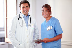 Male doctor and female nurse looking at you Stock Photo