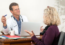 Male Doctor and Female Patient in office. Stock Photo