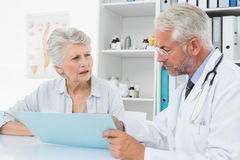 Male doctor with female patient reading reports Stock Photos