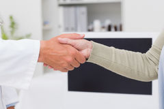 Male doctor and female patient shaking hands Stock Photos