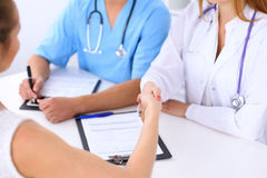 Male doctor and female patient shaking hands. Partnership, trust and medical ethics concept Stock Photo