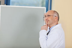 Male Doctor With Finger On Lips Standing By Flipchart Royalty Free Stock Image