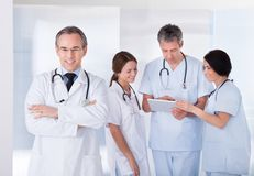 Male doctor in front of team. Male Doctor Standing In Front Of Team Using Digital Tablet Royalty Free Stock Photos