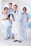 Male doctor in front of team. Male Doctor Standing In Front Of Team Using Digital Tablet Stock Photos