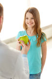Male doctor giving an apple to smiling little girl Stock Images