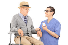 Male doctor giving medications to a senior man Stock Images