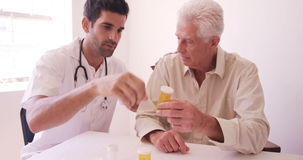 Male doctor giving prescription to senior man stock video