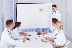 Male doctor giving presentation to colleagues in hospital. Young male doctor giving presentation to colleagues in conference room Stock Photos