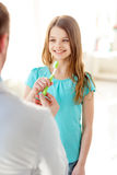 Male doctor giving toothbrush to smiling girl Royalty Free Stock Photography