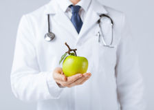 Male doctor with green apple. Close up of male doctor with green apple Royalty Free Stock Photo