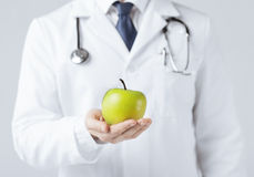 Male doctor with green apple Royalty Free Stock Image