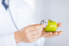 Male doctor with green apple and stethoscope Stock Image