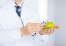 Male doctor with green apple and stethoscope Stock Images