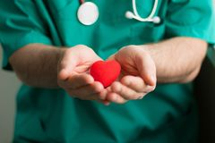 Male doctor in green costume with stethoscope holds in hands bright red heart. Horizontal, healthcare, preventive treatment, royalty free stock photography