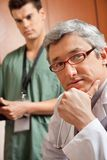 Male Doctor With Hand On Chin. Portrait of mature male doctor with technician in background Stock Photo
