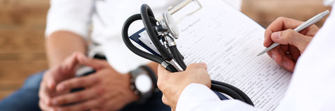 Male doctor hand hold silver pen filling patient history list Royalty Free Stock Image